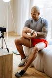 Desportista com músculos agradáveis que filma o vídeo sobre o halterofilismo imagens de stock royalty free