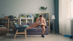 Desportista considerável do indivíduo que faz ocupas com a poltrona no apartamento que aprecia esportes video estoque
