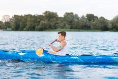 Desportista considerável forte que aprecia seu tempo ao enfileirar na canoa imagens de stock royalty free
