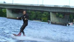 Desportista da energia no roupa de banho preto que wakeboarding Wakeboarder que surfa através do lago vídeos de arquivo