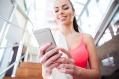 Desportista de sorriso que senta e que usa o telefone celular no gym foto de stock