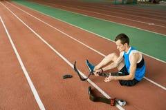 Desportista deficiente que fixa o membro artificial fotografia de stock