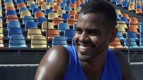 Desportista latino-americano considerável que sorri olhando seus indicadores do resultado, exercício video estoque
