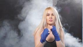 Desportista louro atrativo nas ataduras kickboxing na posição defensiva, movimento lento filme