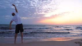 Desportista maduro que faz o exercício da manhã no nascer do sol sobre o mar video estoque