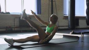 Desportista na esteira do exercício que faz o Abs para malhar no gym Atleta fêmea muscular que faz o exercício do Abs filme