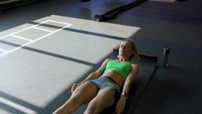 Desportista na esteira do exercício que faz o Abs para malhar no gym Atleta fêmea muscular que faz o exercício do Abs video estoque