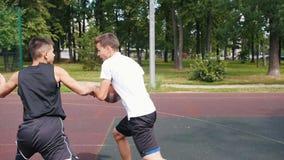 Desportista no t-shirt branco que joga o basquetebol no ar livre da corte com amigo, pingando e jogando a bola vídeos de arquivo