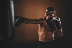 Desportista novo concentrado que treina o encaixotamento tailandês com saco de perfuração Foto de Stock Royalty Free