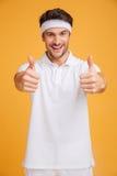Desportista novo considerável alegre que mostra os polegares acima com ambas as mãos fotos de stock royalty free