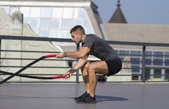 Desportista novo construído Exercícios de prática para as mãos e os ombros imagens de stock royalty free