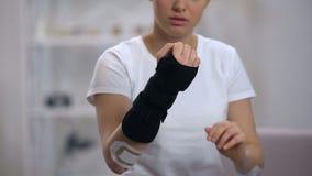 Desportista novo que aplica a reabilitação da cinta do pulso do titã após o traumatismo, saúde vídeos de arquivo