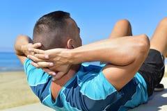 Desportista novo que faz exercícios abdominais Fotografia de Stock
