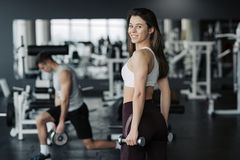 Desportista novo que levanta peso no sportswear vestindo do gym com seu noivo no fundo foto de stock