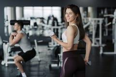Desportista novo que levanta peso no sportswear vestindo do gym com seu noivo no fundo fotos de stock