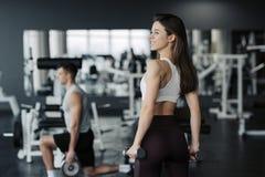 Desportista novo que levanta peso no sportswear vestindo do gym com seu noivo no fundo fotografia de stock royalty free
