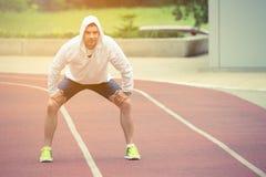 Desportista que descansa na pista de atletismo fora foto de stock