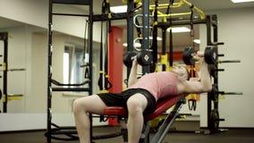 Desportista que faz o exercício da imprensa de banco do peso no gym filme