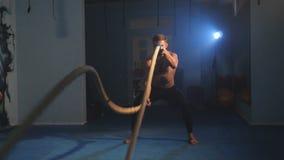Desportista que faz o treinamento pesado da corda no gym video estoque