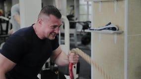 Desportista que faz o treinamento pesado da corda no gym filme
