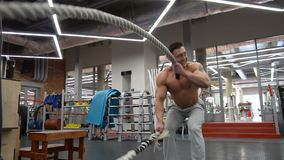 Desportista que faz o treinamento pesado da corda no gym vídeos de arquivo
