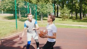 Desportista três que joga o basquetebol na corte no ar livre - um homem que joga a bola para a cesta e marcar filme