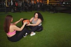 Desportistas positivos bonitos do tamanho que exercitam no gym junto imagem de stock royalty free