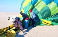 Después de aterrizar a un equipo de ayudantes embala encima de un globo del aire caliente