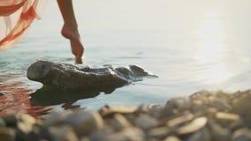 Después de pies femeninos descalzos que caminaban y que salpicaban en ondas de la agua de mar, el steadicam cinemático tiró almacen de metraje de vídeo