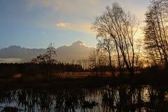 Después de puesta del sol el cielo sobre paisaje del humedal del invierno con el árbol desnudo siluetea el reflejo en el agua Imagenes de archivo