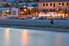 Después de puesta del sol un pescador espera sus pescados en la orilla de la playa foto de archivo libre de regalías