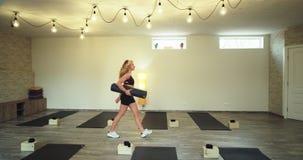 Después de una mujer de la sesión de la meditación de la yoga que toma su estera del deporte y que va derecho del estudio de la y metrajes