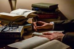 Después de una noche larga estudiar al estudiante continúa leyendo y escribiendo imagen de archivo libre de regalías