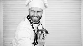 Despu?s de su receta preferida Cocinero del cocinero en la situaci?n uniforme con el plato delicioso Comida de la porci?n del mae fotografía de archivo libre de regalías