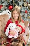 Dess så keligt och mjukt Lyckligt le för småbarn med gåvor Liten flicka med den gulliga kaninen på julgranen litet arkivbild