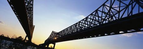 Dessa är de tvilling- broarna som för in i New Orleans De är över den Mississippi floden på solnedgången Arkivbilder