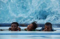 Dessa 3 västra papuanbarn skriker upp till däcket, som det virvla havet är under dem på fartyget Royaltyfri Foto