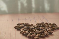 Desserrez les grains de café rôtis sur un traçage d'ECG Image stock