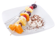 Dessert. A skewer of fresh fruits with chantilly and grazed chocolate Royalty Free Stock Images