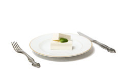 Dessert. In a plate with a plug and a knife isolated on a white background Royalty Free Stock Photos