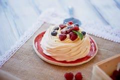 Dessert Anna Pavlova met frambozen en bosbessen op witte houten oppervlakte royalty-vrije stock afbeeldingen