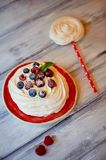 Dessert Anna Pavlova with raspberries and blueberries on white wooden surface. Dessert Anna Pavlova with raspberries and blueberries on white wooden surface Royalty Free Stock Photo