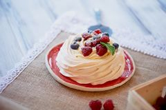 Dessert Anna Pavlova with raspberries and blueberries on white wooden surface. Dessert Anna Pavlova with raspberries and blueberries on white wooden surface Royalty Free Stock Images