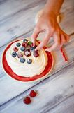 Dessert Anna Pavlova with raspberries and blueberries on white wooden surface. Dessert Anna Pavlova with raspberries and blueberries on white wooden surface Stock Images