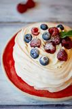 Dessert Anna Pavlova with raspberries and blueberries on white wooden surface. Dessert Anna Pavlova with raspberries and blueberries on white wooden surface Royalty Free Stock Photography