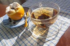 Dessert arancio e cappuccio di vetro di tè con il cucchiaino dorato Fotografie Stock Libere da Diritti
