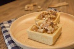 Dessert au goût âpre d'écrou délicieux frais de caramel de plat en bois Image libre de droits