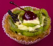 Dessert - a basket with cream, cherries and kiwi on a burgundy background royalty free stock photography