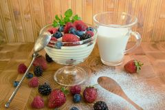 Dessert with berries with a cup of milk and a silver spoon stock images