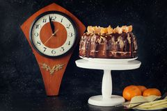 Dessert cake with chocolate icing decorated with tangerines on a black background. Clock wooden royalty free stock photos